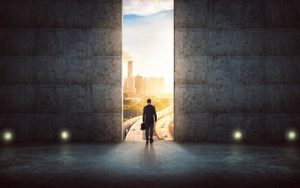 Hesitant businessman looking outside against concrete wall with huge door ,sunrise scene city skyline outdoor view .