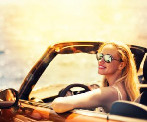 Young Caucasian woman in cabriolet car near sea